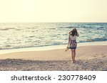young and beautiful woman in colorful dress walking on the beach near the ocean and looking far away at the sunset