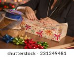 woman wrapping gifts   looks... | Shutterstock . vector #231249481