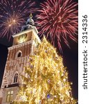 New Year's Eve fireworks over historical Town Hall on the Main Market Square in Krakow - stock photo