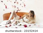 bride lays on a bed. petals of... | Shutterstock . vector #23152414