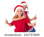 Two happy kids in Christmas hats together with thumbs up sign - stock photo