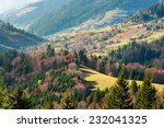 autumn slope of mountain range with coniferous forest and village - stock photo