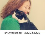 Stock photo beautiful young woman with monochrome black and white cat with retro toning 232253227