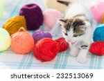 Stock photo white kitten plays with balls of yarn 232513069