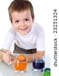 Happy boy smiling while dyeing the easter eggs - isolated - stock photo
