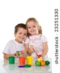 Happy kids painting the easter eggs together - isolated - stock photo