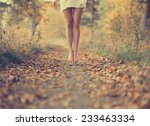 Small photo of Beautiful female legs in the autumn road