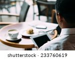 man using digital tablet while... | Shutterstock . vector #233760619