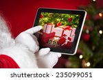 Santa Holding A Tablet With...
