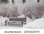 Snow Covered Bench In City Par...