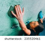 young woman climbing up on wall ... | Shutterstock . vector #235520461