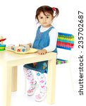 little girl sitting at a table... | Shutterstock . vector #235702687