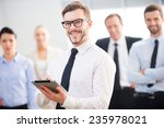 Small photo of Confident business expert. Confident young businessman holding digital tablet and smiling while his colleagues standing in the background