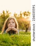 little girl lying on the grass | Shutterstock . vector #236035591