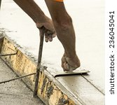 Small photo of Concrete construction contractor using a edger tool on a sidewalk, curb and storm drainage gutter on a new urban road street project