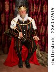 Small photo of King in tudor costume sitting on his throne holding his scepter