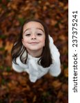Small photo of Cute close up portrait of little girl standing on colorful leaves outdoor in fall. Forest foliage. Smiling happy and excited. Entertainment in autumn outdoors.Beautiful adorable wench.