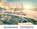 Airplane at the terminal gate preparing the takeoff - Modern international airport with boarding aircraft during sunset - Concept of alternative lifestyle and permanent traveling around the world