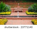 Beautiful Red Brick Walkway and Flower Garden with Water Fountain and Wooden Bench - stock photo