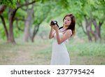 young lady with camera outside | Shutterstock . vector #237795424