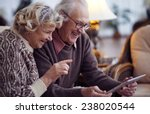 Stock photo elderly husband and wife using digital tablet at home 238020544