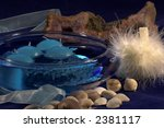 Small photo of Blue tinted bowl with floating blue candles and crystals against a dark blue background, pale blue ribbon , shells at the front and a swansdown powderpuff in front of a large chunk of amethyst stone