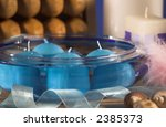 Small photo of Blue tinted bowl with floating blue candles and crystals in the bottom , pale blue ribbon winding through the image, shells at the front and a pink swansdown powderpuff and wooden foot massager