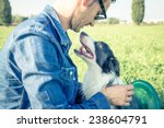 Stock photo young man stroking his playful dog cool dog and young man having fun with frisbee in a park 238604791