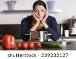 Small photo of Unmotivated attractive young woman preparing the dinner leaning on the hob eyeing the fresh vegetables with a listless glum expression as she stands in her kitchen in an apron