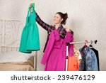 Smiling Girl Holds Two Dresses...