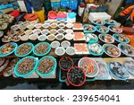 Fresh shellfish for sale in Jagalchi Fish Market under available light