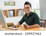 happy man sitting at his... | Shutterstock . vector #239927461