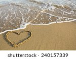 heart drawn on the sand of a... | Shutterstock . vector #240157339