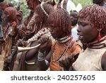 Small photo of Woman blaring trumpet during bulljumping Rital of Hamar tribe. Africa, south Ethiopia