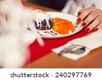 Haute cuisine concept. Woman's hand with perfect manicure and ice cream brownie sundae with chocolate sauce and slices of date plum on white plate. Close up. Indoor shot - stock photo