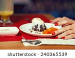 Haute cuisine concept. Woman's hands with perfect manicure and ice cream brownie sundae with chocolate sauce and slices of date plum on white plate. Close up. Indoor shot - stock photo