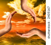 Recycling symbol made from hands over colorful sunset over ocean environmental concept - stock photo