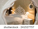 Stock photo white vintage style carved bed and nightstand with lamps sen through the carved mirror 241527757