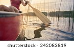 Woman Canoeing At Sunset On...
