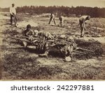 Small photo of African American soldier of a burial party on battle-field of Cold Harbor seated next to a stretcher containing remains of Union soldiers who perished in the battles of Gaines' Mill and Cold Harbor.
