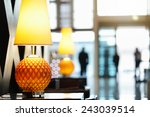 Stock photo reception area in luxury hotel close up on lamp with people traveling in and out the front entrance 243039514