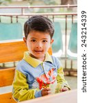 Small photo of TACHILEIK - JANUARY 10:An unidentified kid is smiling at downtown of Tachileik on January 10, 2015 in Tahkeelek,Myanmar.Most of Burmese use powder puff from kanaka plant on face