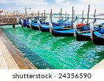 Blue and black gondola boats moored in Venice - stock photo