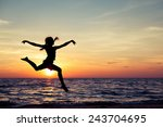 happy girl jumping on the beach ... | Shutterstock . vector #243704695