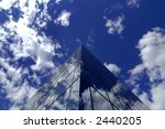 Office building details reflecting, blue sky and clouds in windows - stock photo
