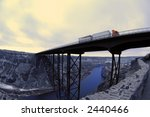 Truck driving over long bridge spanning a ravine - stock photo