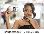 Young black woman taking a selfie inside an airport - stock photo