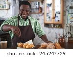 happy young man powdering buns... | Shutterstock . vector #245242729