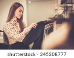 young woman choosing clothes on ... | Shutterstock . vector #245308777