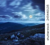 composite mountain landscape. valley with white sharp boulders on the hillside edge in high mountain at night in full moon light - stock photo